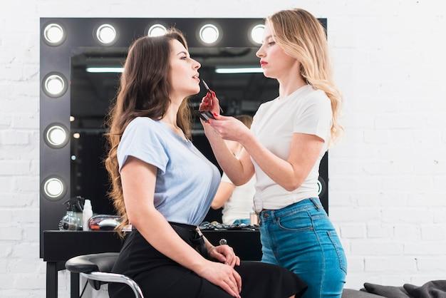 Mujer maquilladora pintando labios de cliente.