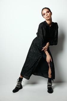 Mujer con maquillaje brillante en moda vestido negro