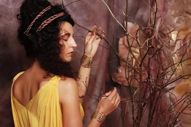 Mujer con maquillaje brillante con ramas secas