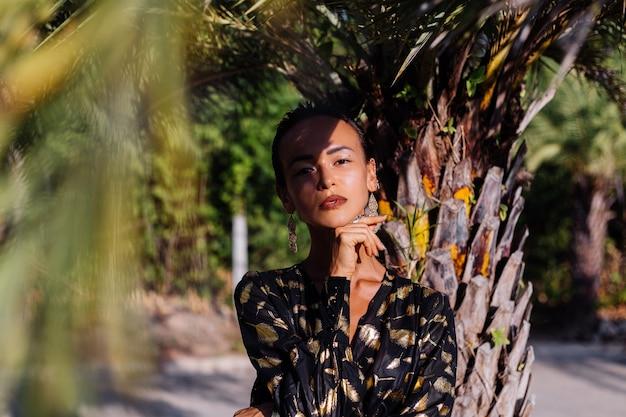 Mujer con maquillaje de bronce en vestido negro dorado cerca de una palmera