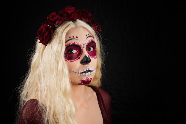Mujer con maquillaje de calavera de azúcar y cabello rubio aislado en pared negra.