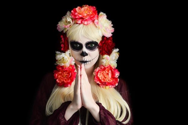 Mujer con maquillaje de calavera de azúcar y cabello rubio aislado sobre fondo negro. dia de los muertos. víspera de todos los santos.