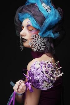 Mujer con maquillaje creativo sosteniendo un ramo de joyas