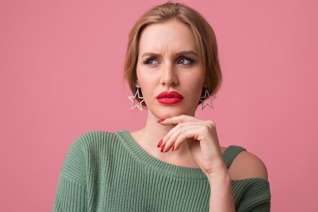 Mujer con maquillaje elegante, labios rojos, suéter verde posando en rosa