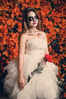 Mujer con maquillaje fantasma y vestido de novia sosteniendo una rosa.