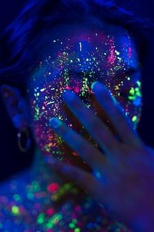 Mujer con maquillaje fluorescente y mano en la cara