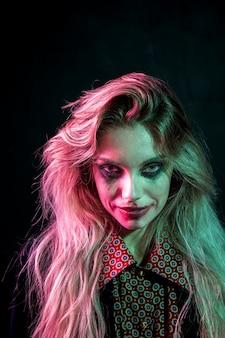 Mujer con maquillaje joker de halloween mirando a cámara