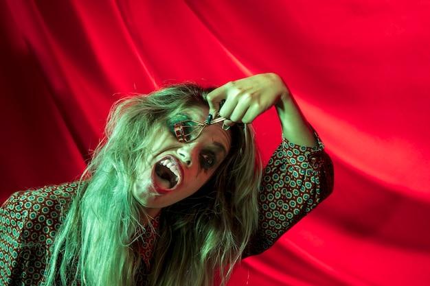 Mujer con maquillaje joker de halloween y rizador de pestañas