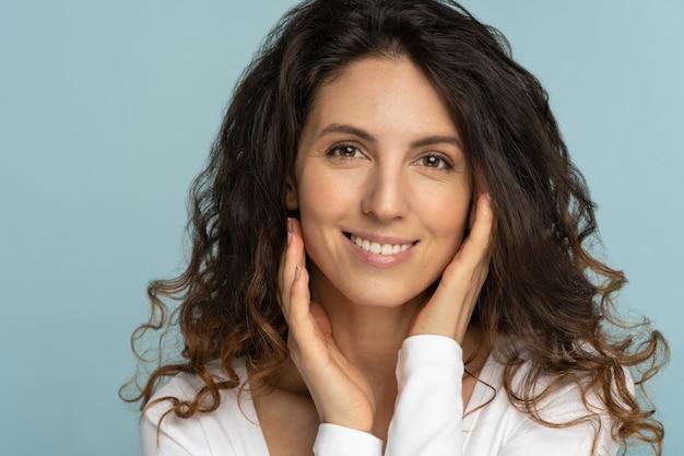 Mujer con maquillaje natural, cabello rizado, tocando la piel pura bien cuidada en la cara, aislado sobre fondo azul.