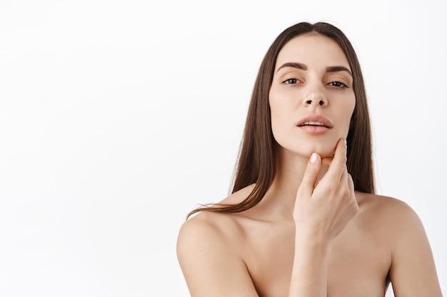 Mujer con maquillaje natural y retrato de piel sana. modelo femenino hermoso que toca la piel facial hidratada que brilla intensamente fresca en el primer de la pared blanca. concepto de cuidado de la piel