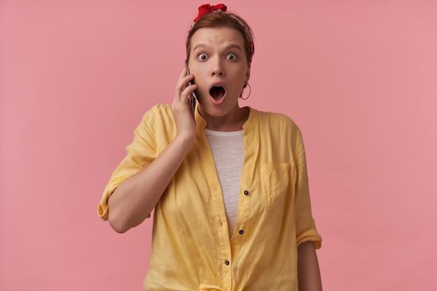 Mujer con maquillaje natural vestida con camiseta blanca y camisa amarilla y pañuelo rojo con brazos gesticula en el teléfono emoción wow sorprendida mirándote en la pared rosa