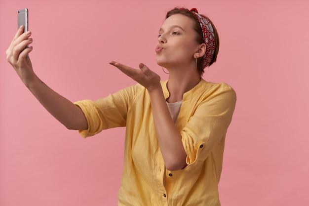 Mujer con maquillaje natural vistiendo elegante traje de verano camisa amarilla y pañuelo rojo emoción coqueteo amoroso y enviar aire beso hacer auto tiro en rosa