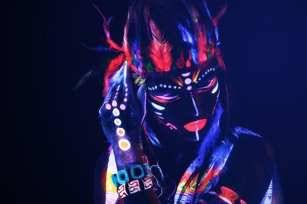 Mujer con maquillaje de neón en luz ultravioleta