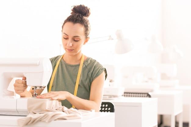 Mujer por máquina de coser