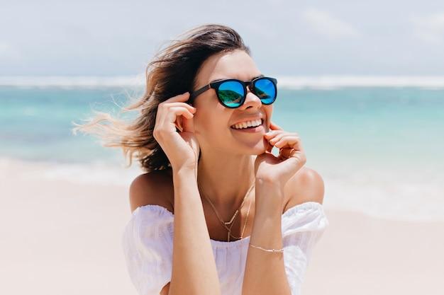 Mujer maravillosa en traje blanco y gafas brillantes posando con expresión de cara feliz en un caluroso día de verano. agradable mujer caucásica de pie cerca del océano en el cielo