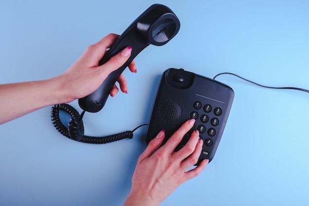 Mujer marcando un número en el teléfono antiguo