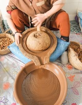 Mujer marroquí moliendo granos de argán en un líquido aceitoso de color marrón espeso. essaouira, marruecos.