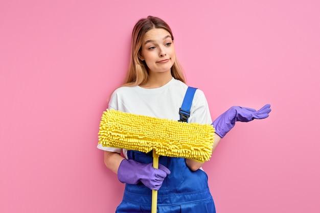 Mujer más limpia sosteniendo un trapeador sobre fondo rosa y mirando a un lado encogiéndose de hombros