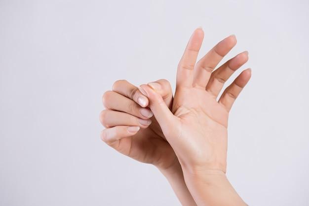 Mujer masajeando su dedo pulgar doloroso, concepto de salud.