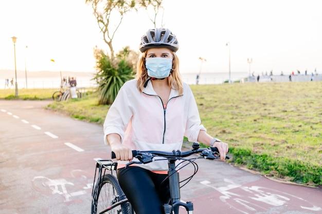 Una mujer con una máscara en la cara con una bicicleta en la ciudad.