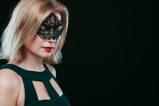 Mujer en máscara de carnaval negro mirando hacia abajo