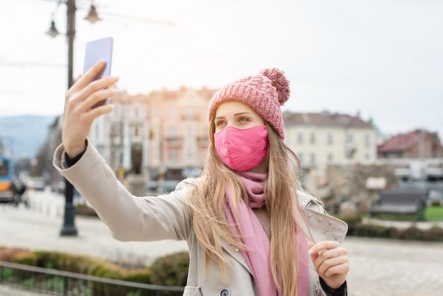 Mujer con máscara de corona haciendo selfie con teléfono