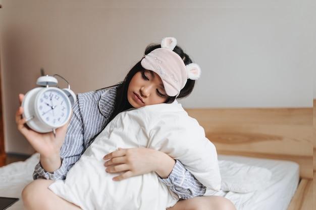 Mujer en máscara de dormir rosa está abrazando la almohada y mirando el despertador con tristeza