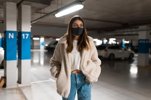 Mujer con máscara en el estacionamiento subterráneo
