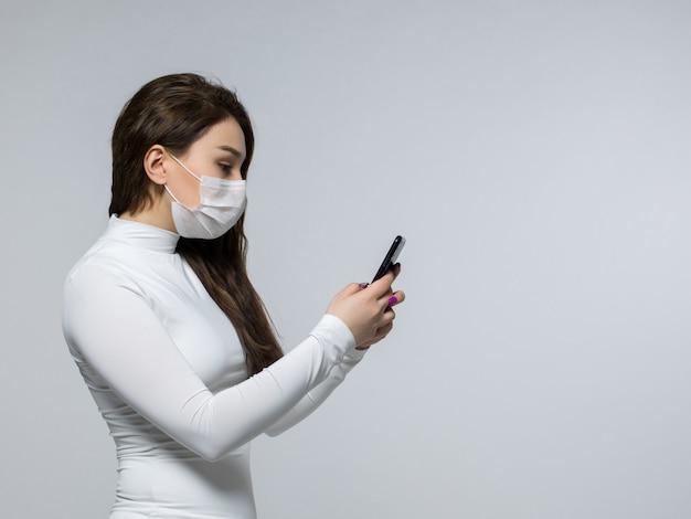 Mujer con máscara estéril blanca mirando su teléfono