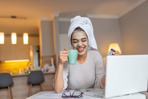 Mujer con máscara facial disfrutando en casa y usando su computadora portátil.