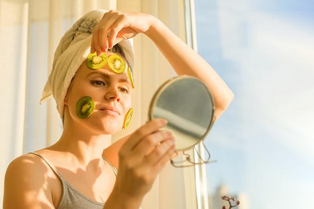 Mujer con máscara facial de fruta casera natural de kiwi en la cara