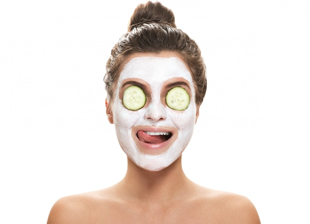 Mujer con máscara facial y rodajas de pepino en los ojos