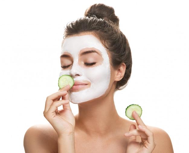 Mujer con máscara facial y rodajas de pepino en sus manos