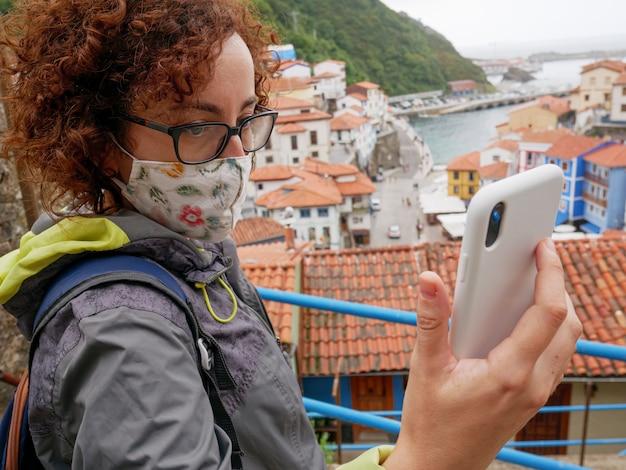 Una mujer con una máscara facial usa su teléfono celular para tomarse un selfie en un pueblo
