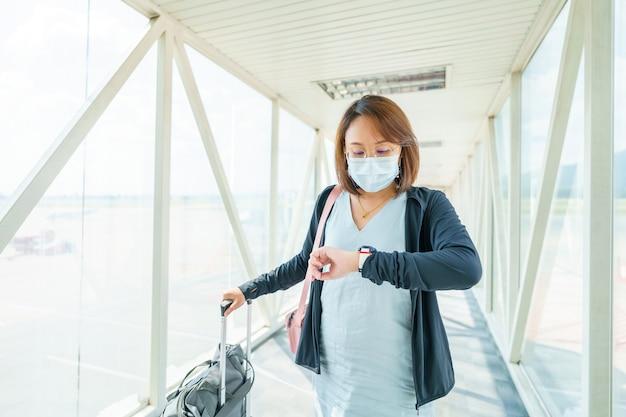 Mujer con máscara facial está viajando en el aeropuerto, nuevo estilo de vida de viaje después del covid-19. el distanciamiento social y el concepto de burbuja de viajes.