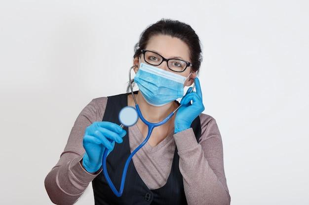 Mujer en una máscara con un fonendoscopio en sus manos