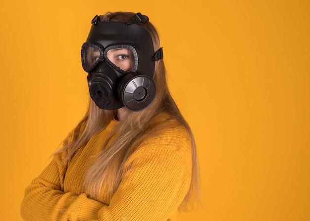 Mujer con máscara de gas sobre fondo naranja