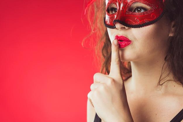 Mujer en máscara gesticular silencio