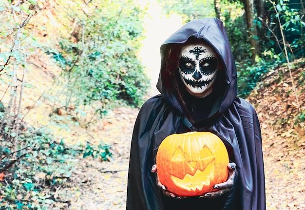 Mujer con máscara de halloween pintada con capucha negra