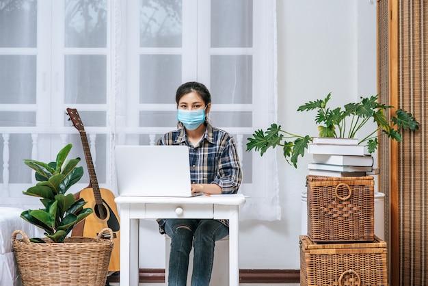 Una mujer con una máscara higiene está sentada en el escritorio con una computadora portátil.
