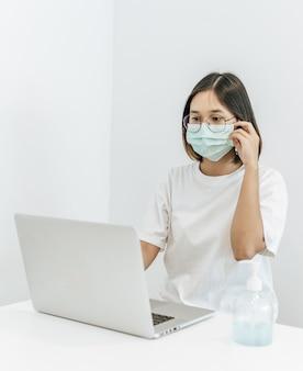 Una mujer con una máscara jugando un portátil y con una botella de gel para lavarse las manos.