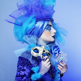 Mujer con máscara en maquillaje teatral creativo