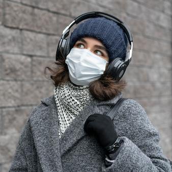 Mujer con máscara médica en la ciudad escuchando música
