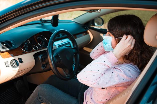 Mujer de la máscara médica en coche. coronavirus, enfermedad, infección, cuarentena, covid-19