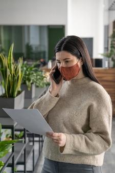 Mujer con máscara médica comprobando notas en el trabajo