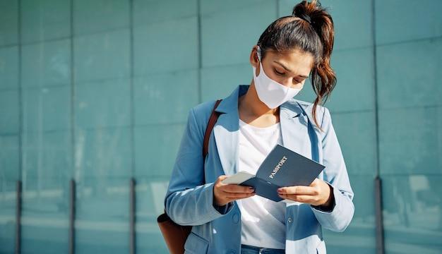 Mujer con máscara médica comprobando su pasaporte en el aeropuerto durante la pandemia