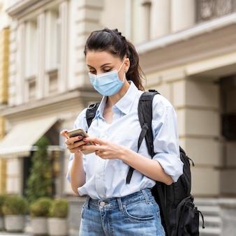 Mujer con máscara médica comprobando su teléfono