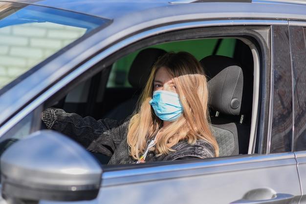Mujer con máscara médica conduciendo un automóvil, mirando a la cámara porque la contaminación del aire o el virus