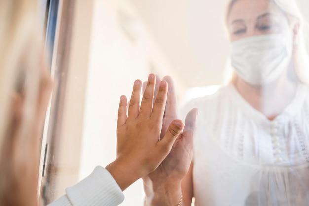Mujer con máscara médica en cuarentena detrás de la ventana con el niño