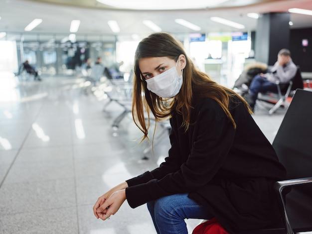 Mujer con máscara médica es aeropuerto esperando vuelo